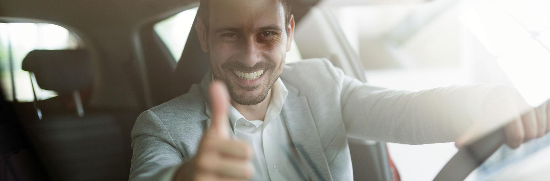 Man sits in the car and shows thumbs up